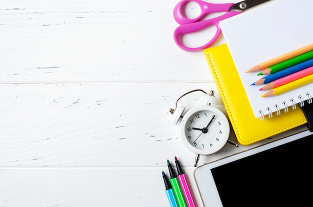 Een tablet met een leeg scherm en kantoorbenodigdheden op een witte houten.