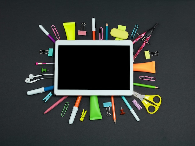Een tablet met een leeg scherm en schoolspullen op een zwarte achtergrond