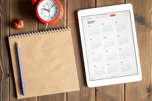 Een tablet met een open kalender voor het jaar 2021, een rode wekker, kastanjes en een notitieboekje van ambachtelijk papier op de achtergrond van een houten planken tafel