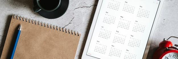 Een tablet met een open kalender voor het jaar 2021, een rode wekker