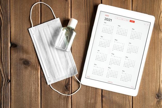 Een tablet met een open kalender voor het jaar 2021 en een beschermend medisch masker en handdesinfecterend middel op een houten planken tafel achtergrond. covid-19 coronavirus-beschermingsconcept in 2021