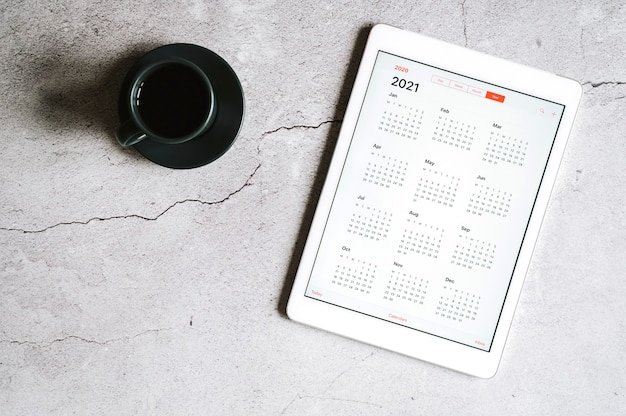 Een tablet met een open kalender voor het jaar 2021 en een kopje koffie op een grijze betonnen achtergrond