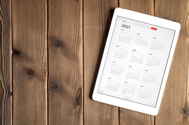 Een tablet met een open kalender voor het jaar 2021 op de achtergrond van een houten planken tafel. ruimte voor tekst