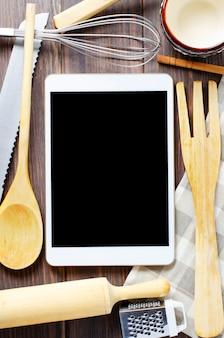 Een tabletcomputer en kookbatterij op een bruine houten lijst. kopieer ruimte. concept van het koken van recepten