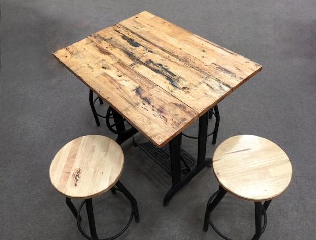 Een tafel gemaakt van houten planken bovenop een naaimachine met ronde stoelen