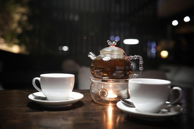 Een tafel in een café met een cocktail en een kopje thee