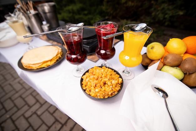 Een tafel met een wit tafelkleed, pannenkoeken en drie glazen met een vulling. camping