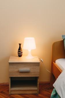Een tafellamp en een decoratieve kan op het nachtkastje bij het bed in een kamer met lichte muren