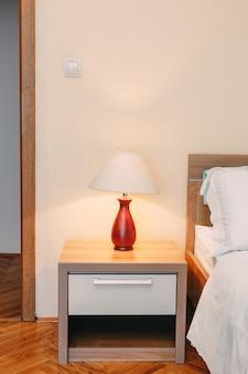 Een tafellamp op een nachtkastje bij het bed in een kamer met lichte muren