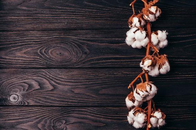 Een tak van droog katoen op een houten oppervlak achtergrond