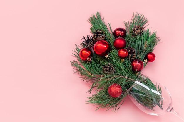 Een tak van een kerstboom met rode speelgoedballen en kegels in een glas geïsoleerd op een roze achtergrond