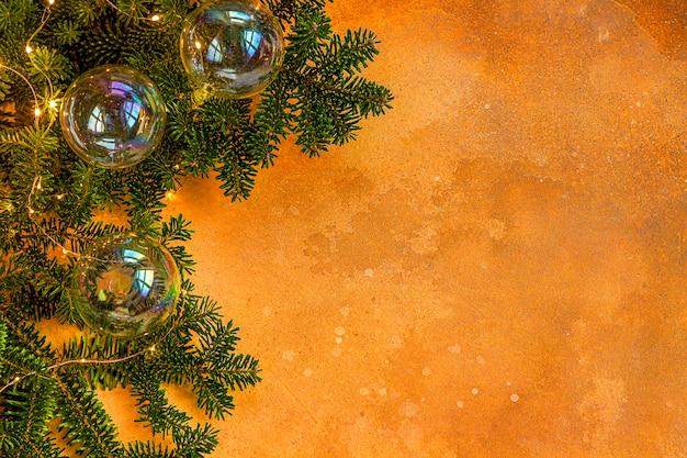 Een tak van sparren met kerstspeelgoed in de vorm van zeepbellen en een slinger op een geel. feestelijke stemming. plat leggen. bovenaanzicht. copyspace.