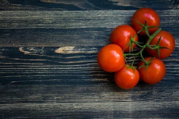 Een tak van verse rode tomaten op een zwarte achtergrond.