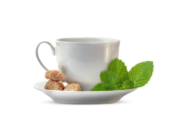 Een takje verse aromatische munt op witte theekop met schotel en suiker op wit