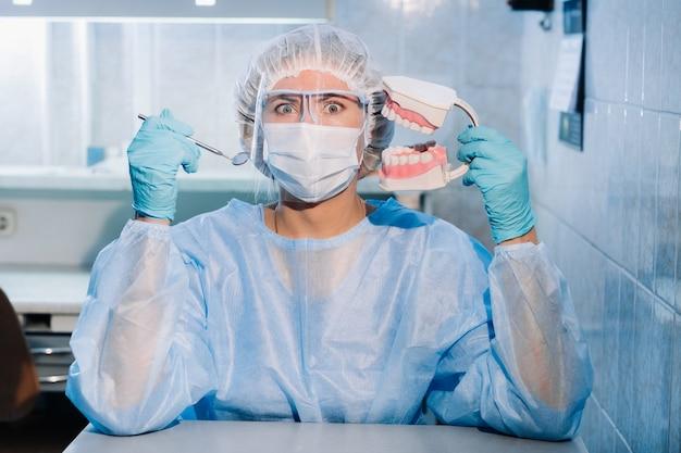 Een tandarts die blauwe handschoenen en een masker draagt, houdt een tandmodel van de boven- en onderkaak en een tandheelkundige spiegel vast.