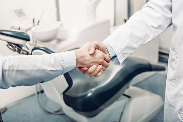 Een tandarts en een patiënt zijn handenschudden