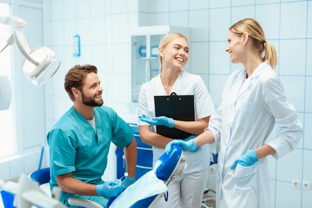 Een tandarts en twee verpleegsters poseren in een tandartspraktijk