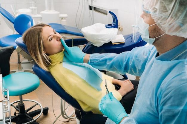 Een tandarts met een beschermend masker gaat naast de patiënt zitten en bedekt zijn mond met een vinger.