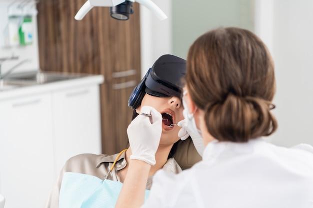 Een tandarts onderzoekt de tanden van haar patiënt op de stoel van de tandarts, terwijl de patiënt een vr-bril draagt