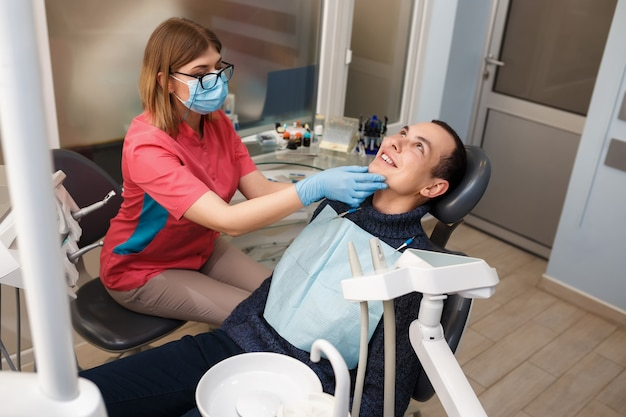 Een tandarts onderzoekt de tanden van zijn patiënt. actie in de tandheelkundige kliniek