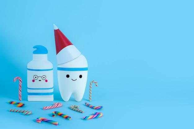 Een tandspeelgoed in een nieuwjaarsmuts naast een tandpasta omringd door veelkleurige zuurstokken