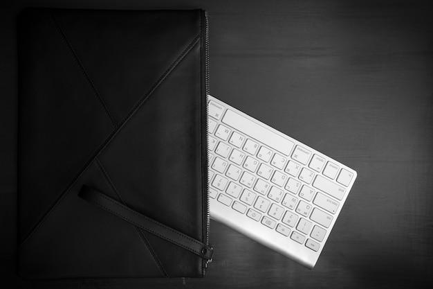 Een tas en toetsenbord zijn onder de vintage getextureerde vloer geplaatst