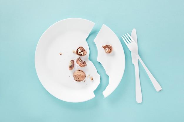 Een te hoge prijs: bord gebroken in een poging een noot te snijden met mes en vork. moeilijke beslissing in een notendop concept, creatieve flatlay met veel copyspace