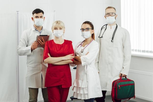 Een team van artsen in beschermende maskers gaat tijdens een coronaviruspandemie de patiënt bezoeken.