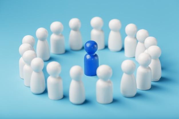 Een team van blanken staat rond en luistert naar de blauwe leider van de leider. het concept van de leider van het zakelijke team.