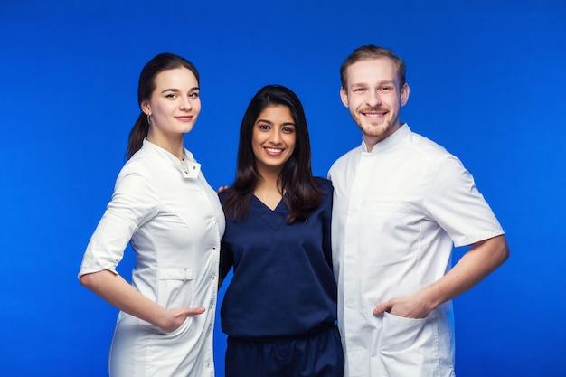 Een team van jonge artsen. multinationale mensen - arts, verpleegster en chirurg op blauwe achtergrond. een groep geneeskundestudenten van verschillende nationaliteiten kijkt in de cel.