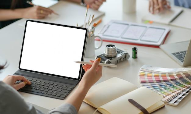 Een team van professionele ontwerpers werkt met smartphones en laptops om applicaties te ontwerpen.