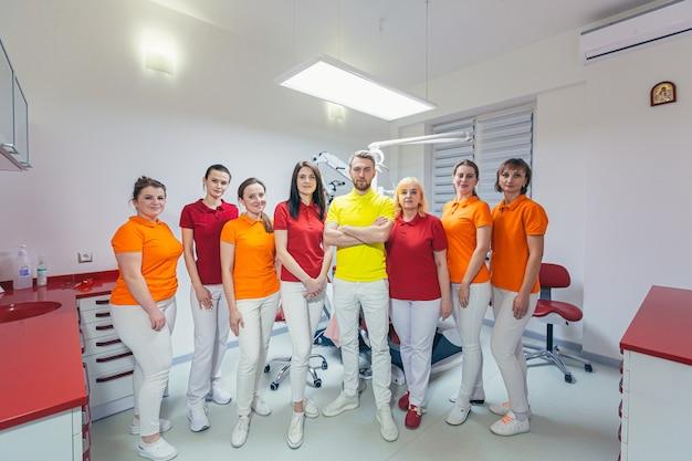 Een team van tandartsen in volgroeide medische vormen staat bij de kliniek