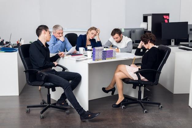 Een team van vijf mensen heeft een vergadering op kantoor