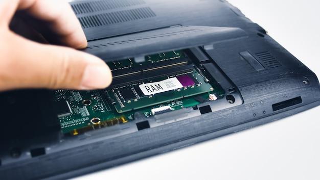 Een technicus inspecteert het ram-geheugen van een laptop door het deksel te openen (random access memory)