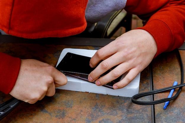 Een technicus repareert en vervangt het gebroken scherm op een smartphone