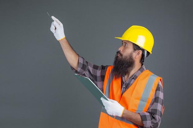 Een technische man met een gele helm met een ontwerp op een grijs.
