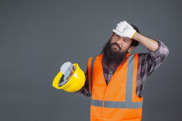 Een technische man met een gele helm met witte handschoenen toonde een grijs gebaar.