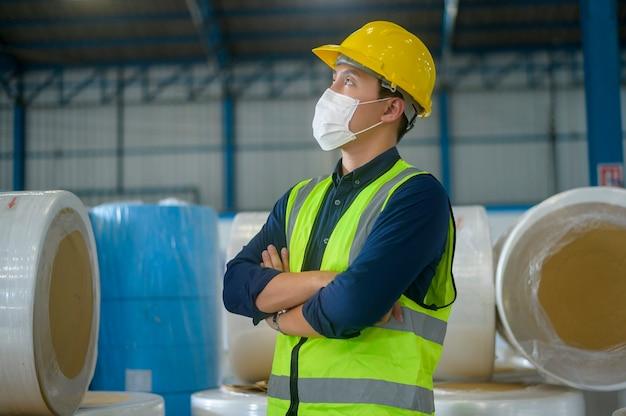 Een technische man met een medisch masker, een beschermende helm die in een magazijnfabriek werkt
