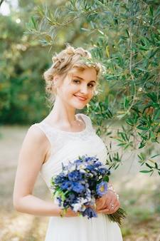 Een tedere bruid met een boeket blauwe bloemen in haar handen staat bij groene olijftakken in een bosje
