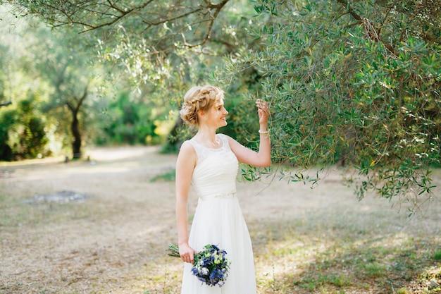 Een tedere bruid met een boeket blauwe bloemen staat bij een olijfboom en raakt de takken mee