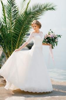 Een tedere bruid staat in de buurt van een palmboom en houdt een bruidsboeket en de rand van haar rok vast