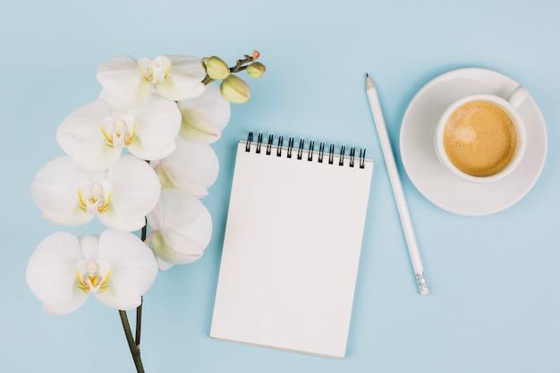 Een tedere witte orchidee bloeit dichtbij de spiraalvormige blocnote; potlood en koffiekopje tegen blauwe achtergrond