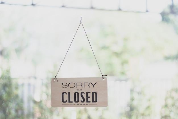 Een teken die van de deur van de koffiewinkel hangen, sluit de achtergrond van het tekenonduidelijke beeld, dicht etiketwoord