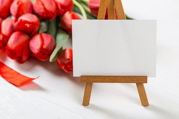 Een teken tegen een van rode tulpen op witte tafel. het concept van moederdag. kopieer ruimte.