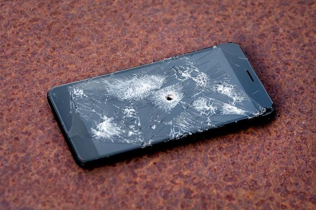 Een telefoon met scheuren en een gat van een kogel