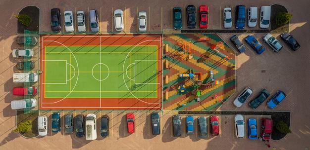 Een tennisbaan is omheind en een parkeerplaats in het centrum van het moderne wooncomplex.