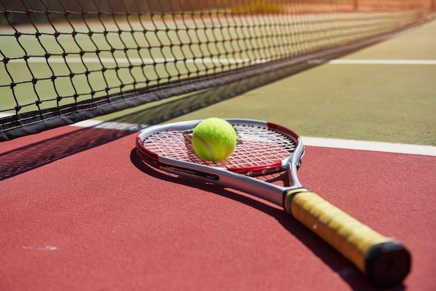Een tennisracket en een nieuwe tennisbal op een pas geschilderde tennisbaan.