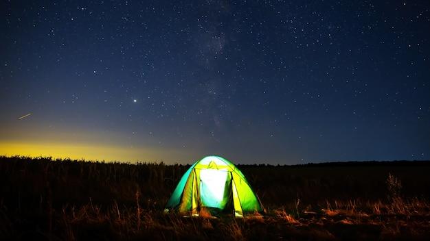 Een tent in een veld met licht van binnen en een lucht vol stralende sterren in moldavië