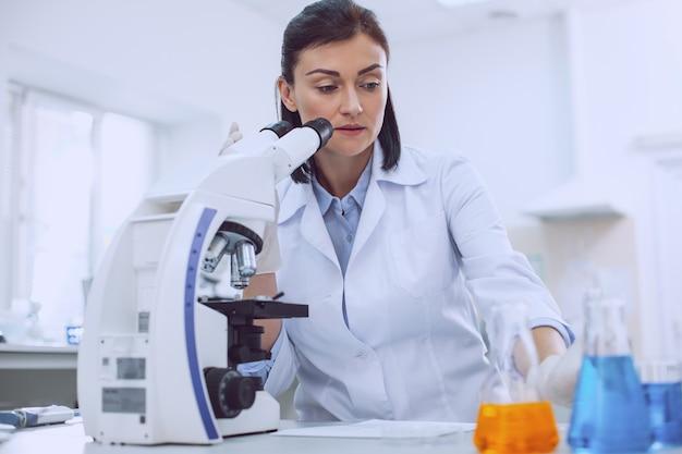 Een test uitvoeren. vastberaden bekwame wetenschapper die met een microscoop werkt en de buisjes aanraakt