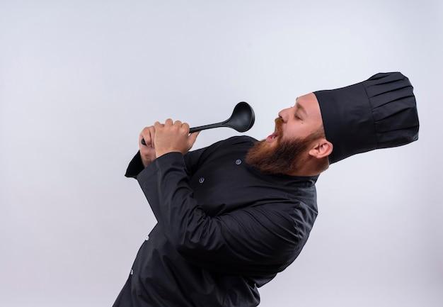 Een tevreden bebaarde chef-kok in zwart uniform zingt met pollepel en gebruikt het als een microfoon op een witte muur